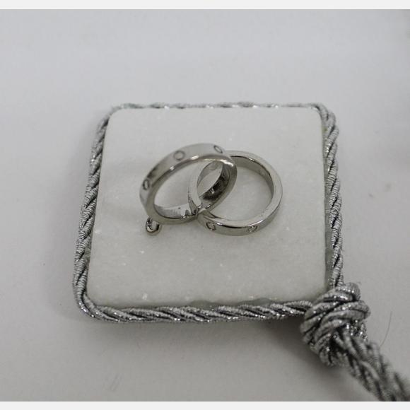 Μπομπονιέρα γάμου μεταλλικές βέρες ασημί πάνω σε πέτρα